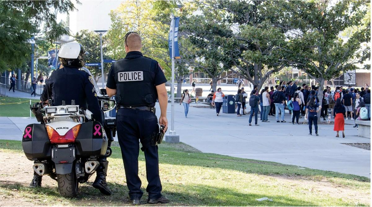 La policía del campus observa cómo se forma una multitud de personas en el Quad durante una manifestación religiosa en la Universidad Estatal de California, Fullerton, el 22 de octubre de 2018. Foto de Riley Mcdougall, The Daily Titan