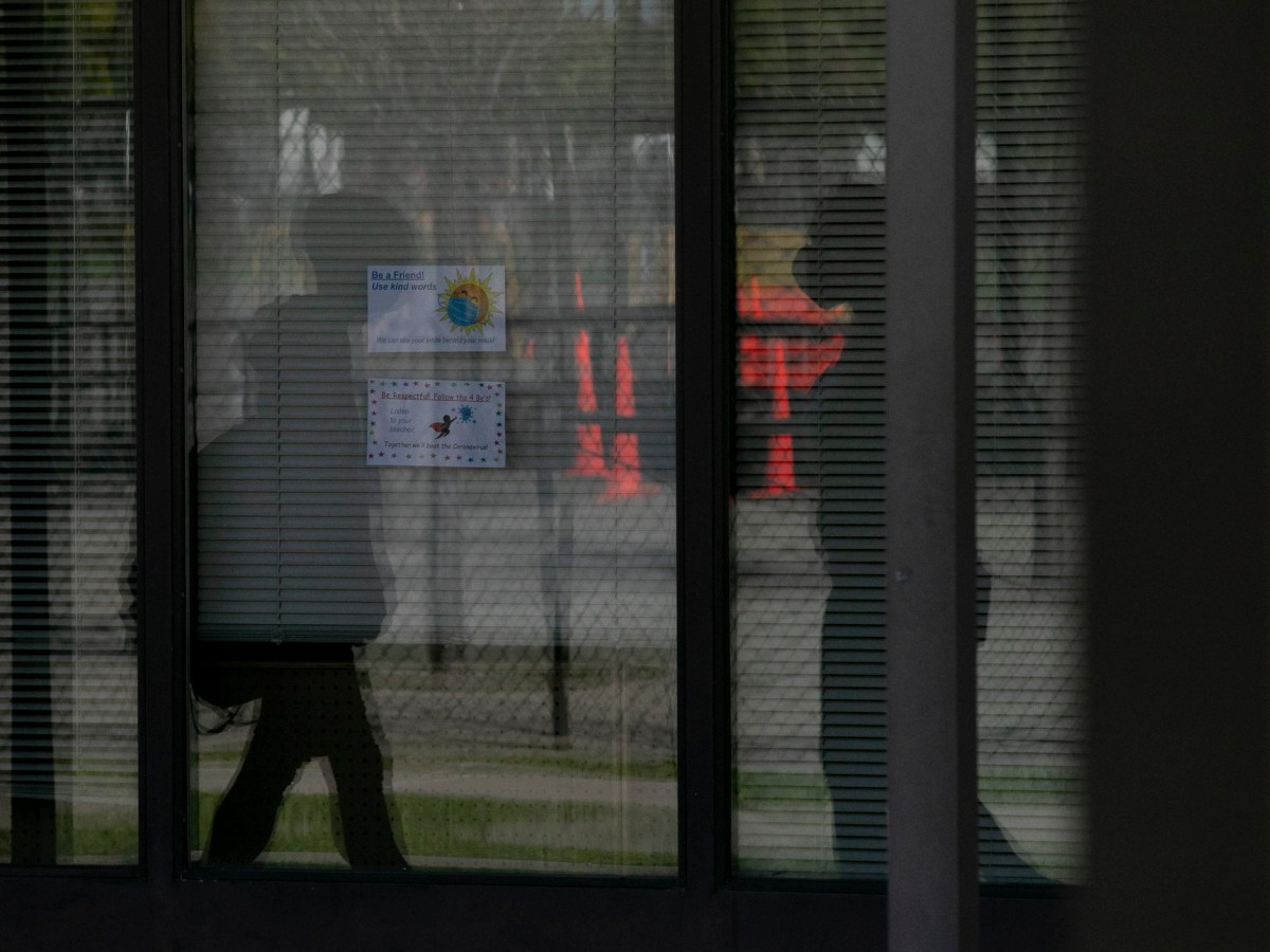 Silhouettes of students walking between buildings are seen reflected in a window at Ruby Bridges Elementary school in Alameda on March 16, 2021. Photo by Anne Wernikoff, CalMatters
