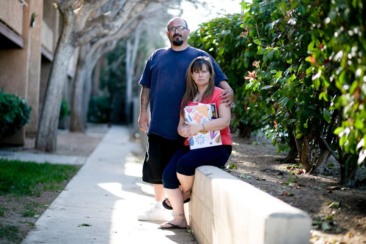 Stacy Lira y su esposo de 28 años, Armando, afuera de su casa en Victorville el 29 de marzo de 2021. Ella sostiene una carpeta llena de papeleo de desempleo. Foto de Shae Hammond para CalMatters