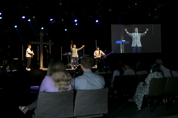 Pastor Ryan Kwon celebrates the resurrection during his Easter sermon at Resonate church in Fremont on April 4, 2021. The space, which typically seats several hundred, had 195 seats to ensure social distancing. Photo by Anne Wernikoff, CalMatters
