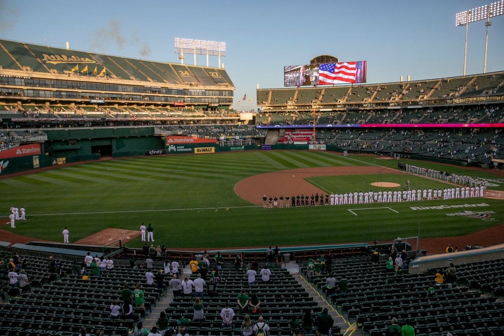 Players and spectators stand for the national anthem at the start of the game between the Oakland A's and the Houston Astros. Oakland Coliseum operated at 26% capacity in order to allow ample spacing between groups. Photo by Anne Wernikoff, CalMatters