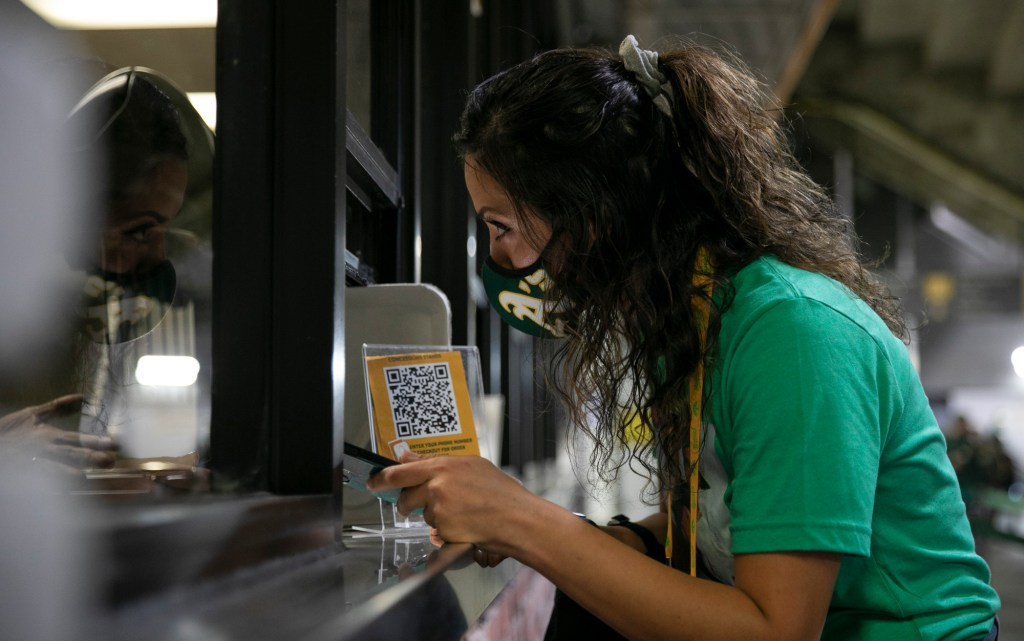 "Talat Mirmalek, of San Francisco, speaks with a concessions employee while struggling to use the online ordering and payment app. ""We're missing the whole first half of the game right now,"" her friend Sierra Coats said in frustration. Photo by Anne Wernikoff, CalMatters"