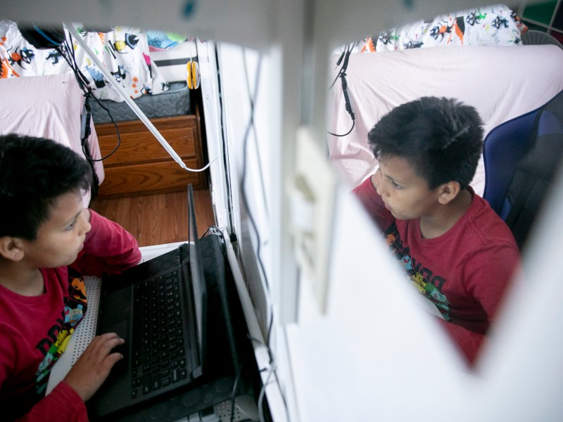 """Mario Ramirez Garcia, 10, attends online class in the bedroom he shares with his sister on April 23, 2021. """"It's funner in real school,"""" said Mario of distance learning. Photo by Anne Wernikoff, CalMatters"""
