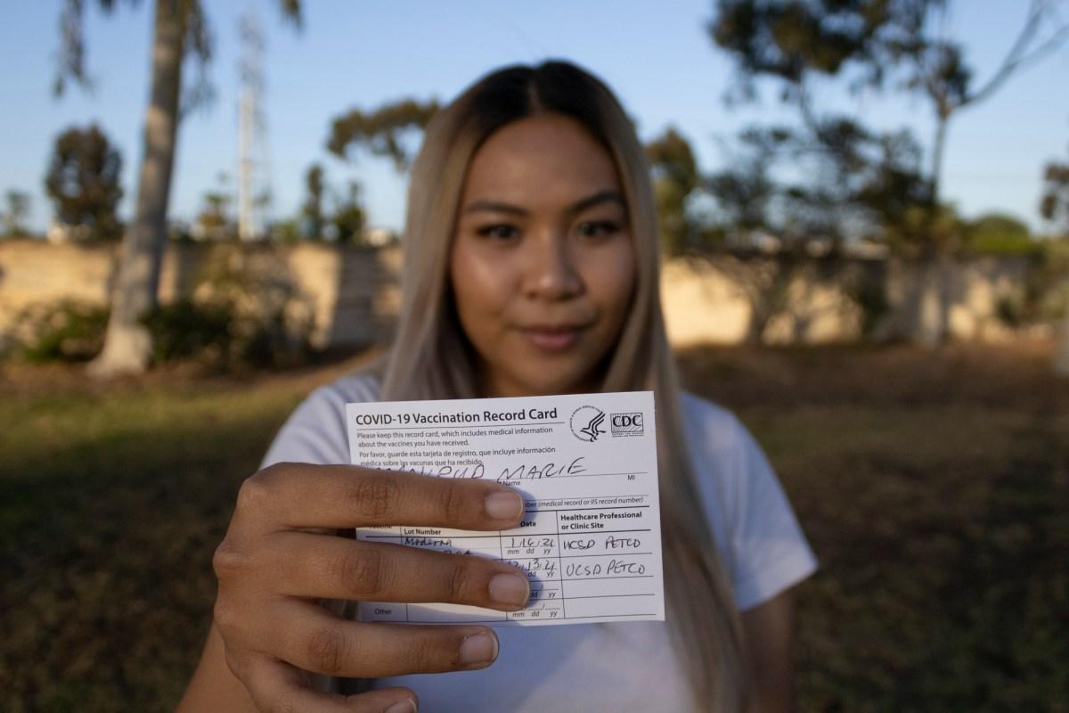 Marie Manipud sostiene su tarjeta de vacunación COVID-19 en Lindbergh Neighborhood Park el 4 de mayo de 2021. Los estudiantes de UC San Diego pueden asistir a una graduación en persona este año con una prueba de COVID negativa o prueba de vacunación. Foto de Arlene Banuelos para CalMatters.