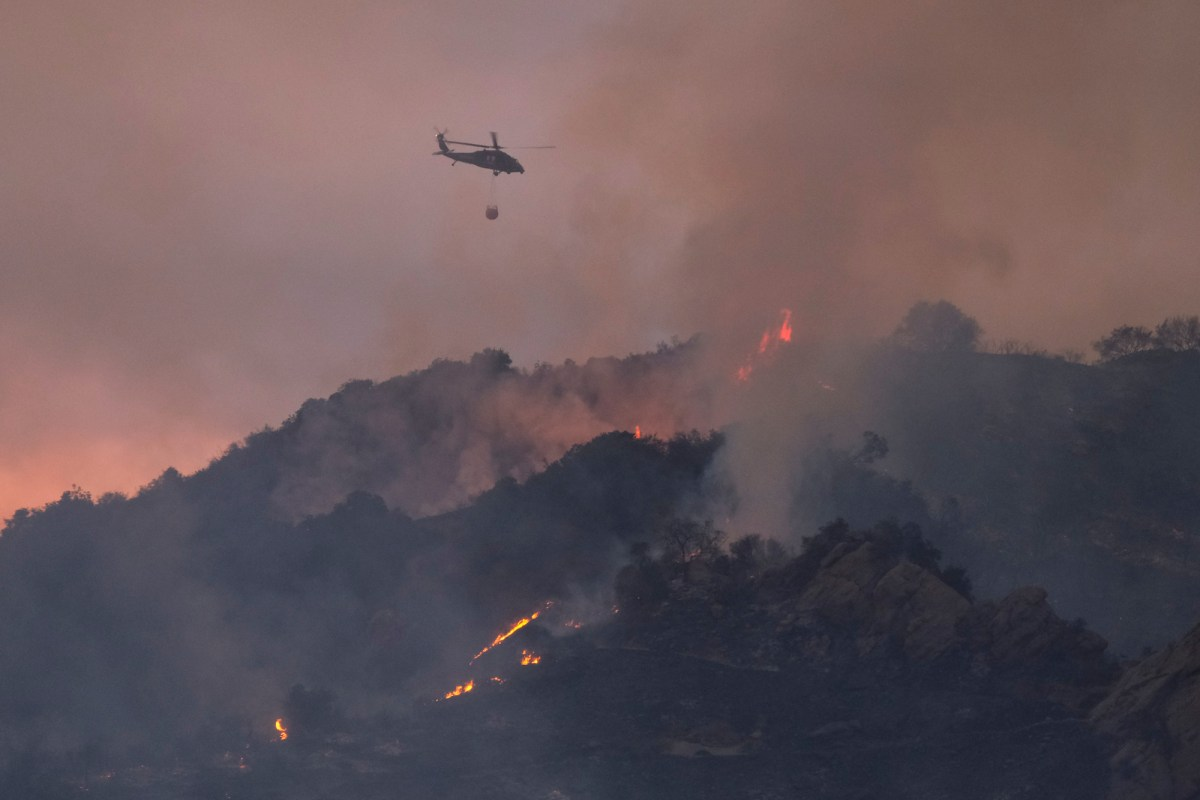 A firefighting helicopter flies away after dropping water over a brush fire scorching at least 100 acres in the Pacific Palisades area of Los Angeles Saturday, May 15, 2021. AP Photo/Ringo H.W. Chiu