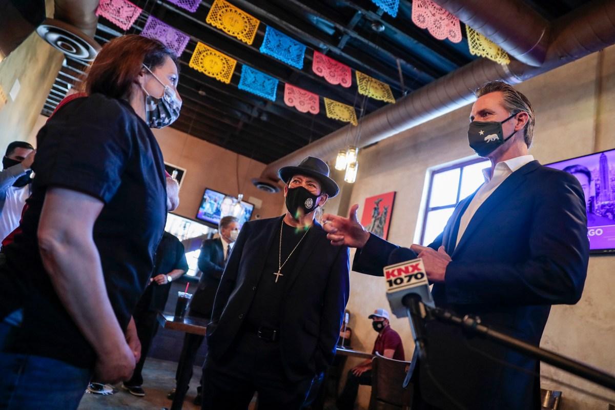 Magaly Colelli, izquierda, propietaria del restaurante de Magaly, conversa con el gobernador Gavin Newsom y el actor Danny Trejo, en el centro, en San Fernando, el 29 de abril de 2021. Foto de Robert Gauthier, Los Angeles Times vía AP/Pool