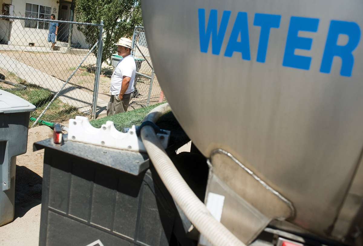 """Rural Latino communities were hit hard in California's last drought. Here """"Aqua Man"""" Sebastian Mejia delivers portable water to the drought-affected houses Thursday, July 16, 2015. Mejia delivers water 5 days a week to a dozen houses a day in the East Porterville area. Photo by Chieko Hara, The Porterville Recorder via AP"""