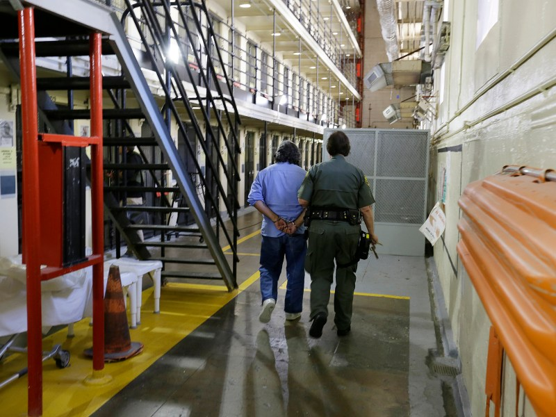 California Gov. Gavin Newsom said he has no plans to require prison employees to get COVID vaccines as a condition of employment. Here a condemned inmate is escorted by a guard back to his cell at San Quentin State Prison in this 2016 file photo by Eric Risberg, AP Photo