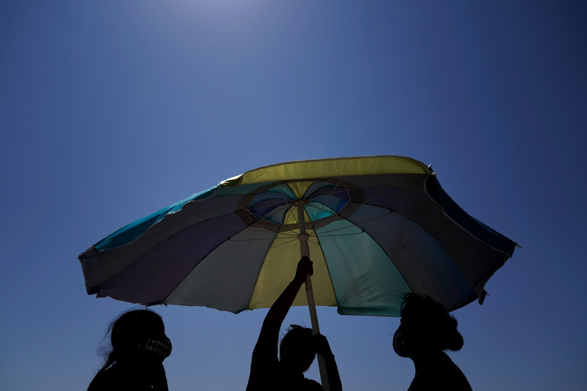 Beach goers set up an umbrella in Huntington Beach during a sweltering heat wave over Labor Day weekend on Sept. 5, 2020. Photo by Jae C. Hong, AP Photo