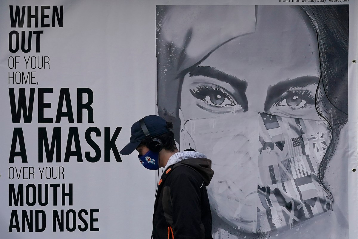 """Apedestrian passes a mural reading: """"When out of your home, Wear a mask over your mouth and nose,"""" in San Francisco on Nov. 21, 2020. Photo by Jeff Chiu, AP Photo"""