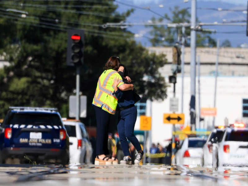 Two people hug near the scene of a mass shooting at a Valley Transportation Authority light rail yard in San Jose on May, 26, 2021. An employee opened fire Wednesday killing eight people before taking his own life. Photo by Randy Vazquez, Bay Area News Group