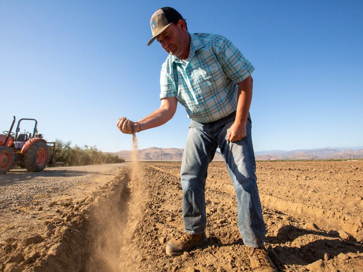 John Werner holds a handful of soil for a portrait in his soon-to-be pistachio grove near Visalia on June 10, 2021. He works as an educator to supplement his income from farming and is planning on planting pistachio trees soon. Photo by Shae Hammond for CalMatters