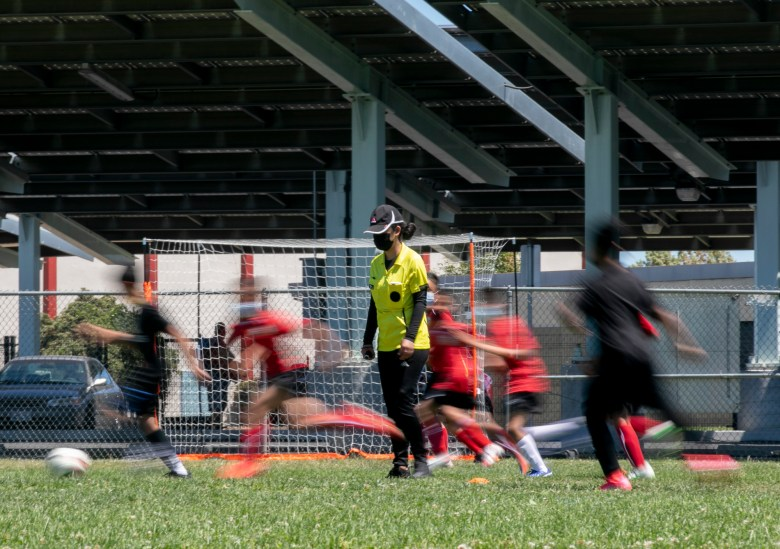 Players run past Claudeth as she referees a soccer game for a local children's league. Photo by Anne Wernikoff, CalMatters