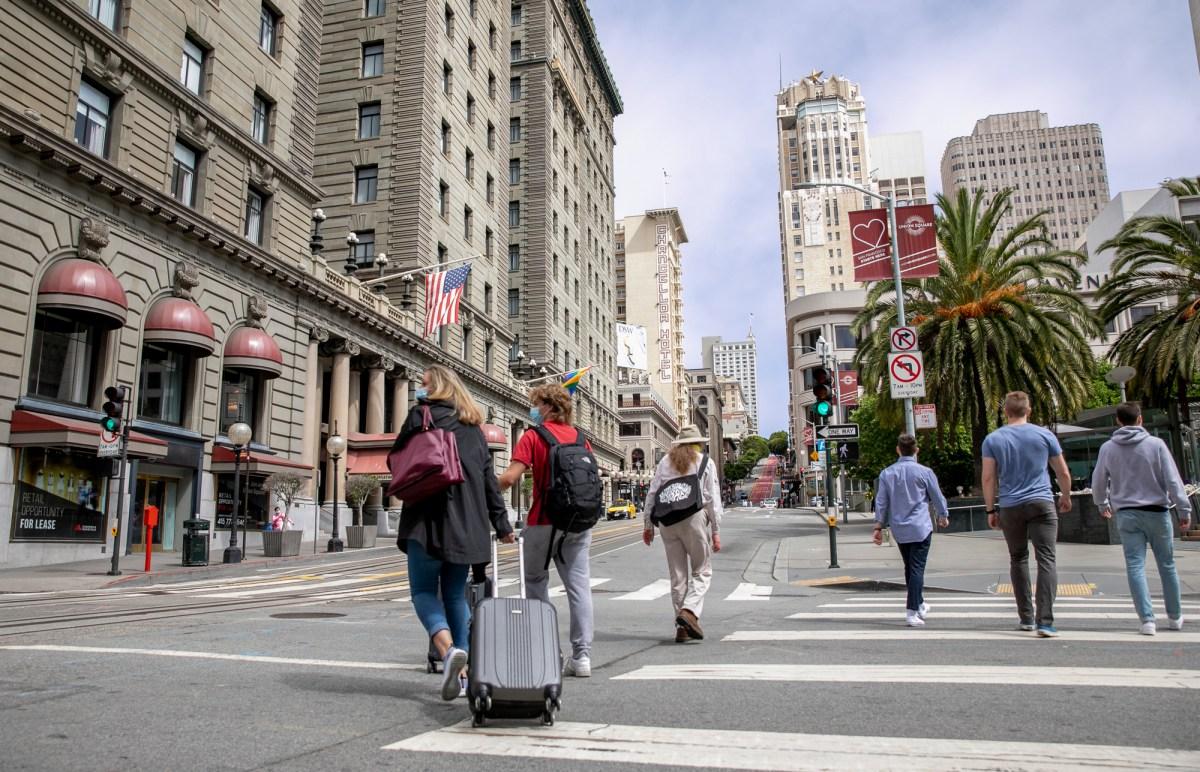 Peatones con maletas caminan por Union Square en San Francisco el 14 de junio de 2021. La intersección de las calles Geary y Powell habría estado llena de tráfico, tranvías y multitudes antes de la pandemia. Foto de Anne Wernikoff, CalMatters