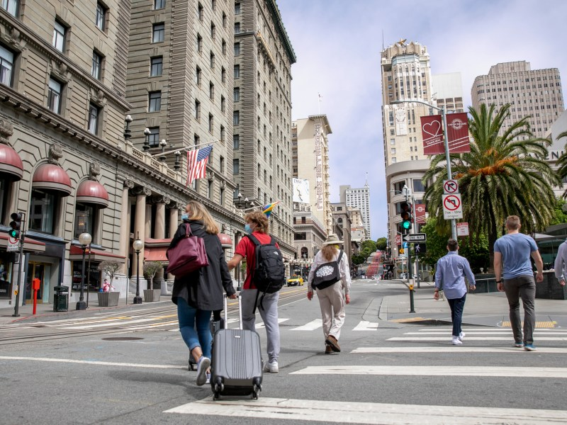 Pedestrians with suitcases walk through union square in San Francisco on June 14, 2021. The intersection of Geary and Powell Streets would have been busy with traffic, street cars and throngs of foot traffic before the pandemic. Photo by Anne Wernikoff, CalMatters
