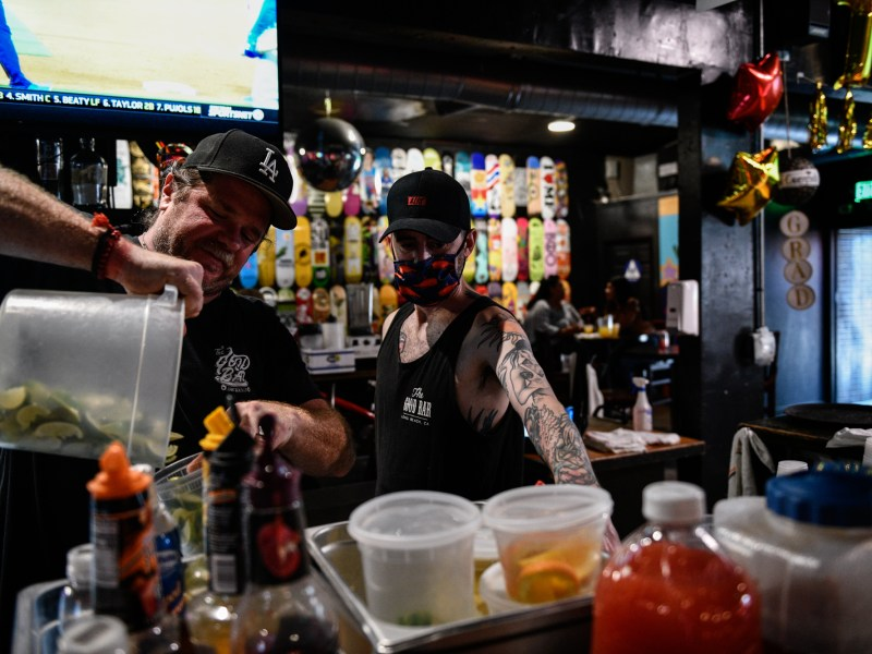 Joshua Rayburn, with a mask on, and Blake Whytock, without a mask, prepare drinks for customers inside The Good Bar in Long Beach, on June 15, 2021. Rayburn has decided he wants to wait before being maskless inside public spaces. Pablo Unzueta for CalMatters