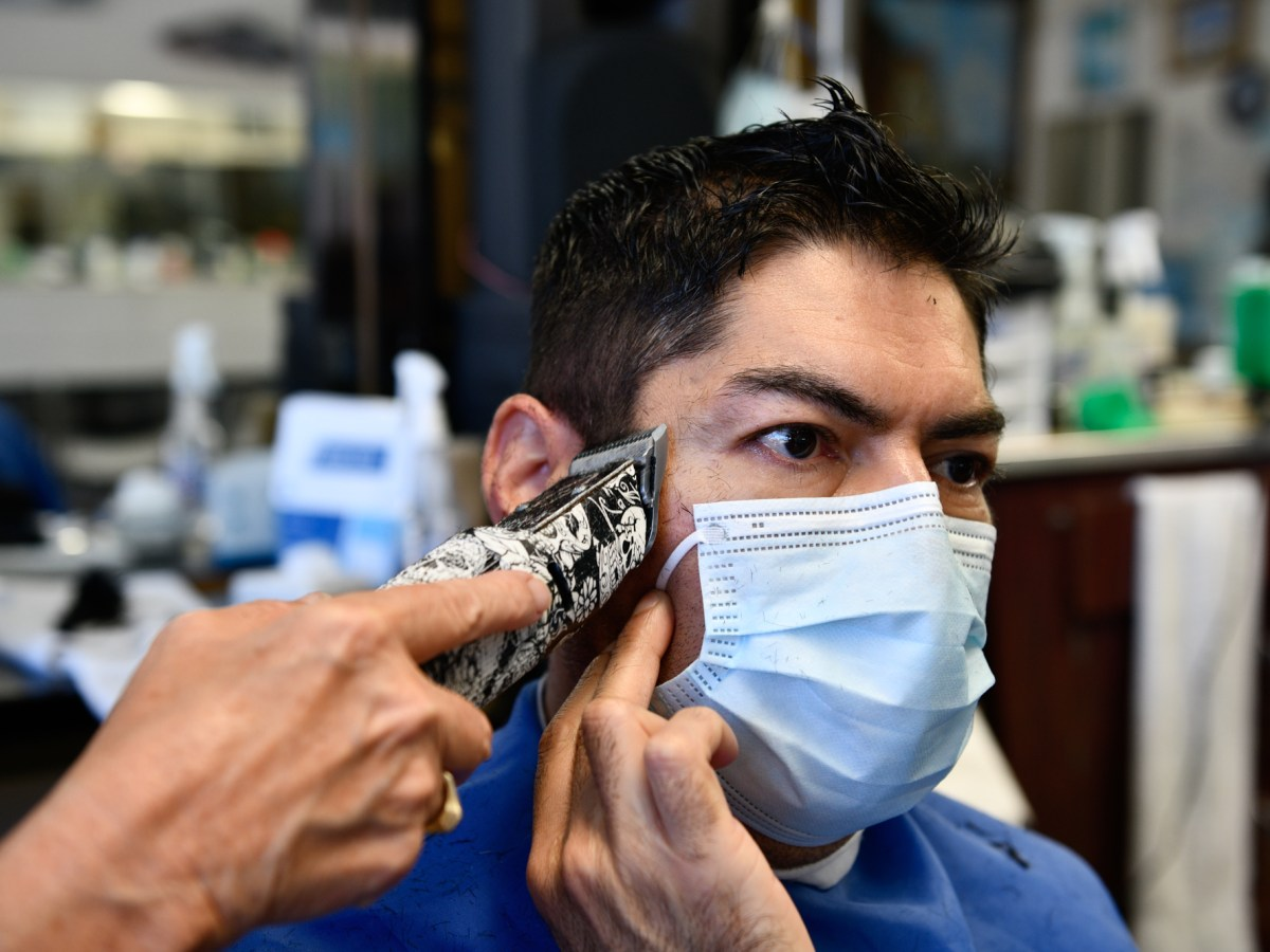 """Carlos Hernandez holds his mask while getting a haircut from Sarah Cordiey at Spiros Barber Shop in Long Beach, on June 9, 2021. """"During the pandemic, I got depression and anxiety,"""" said Hernandez, who saw his family last week for the first time in more than a year. """"But then when I got [fully] vaccinated I felt a lot better."""" Pablo Unzueta for CalMatters"""