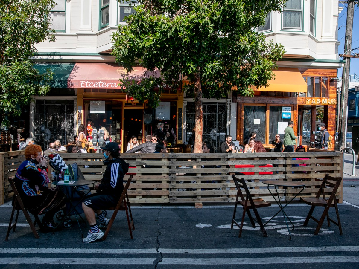 Restaurant patrons sit in a parklet along Valencia Street in San Francisco on July 25, 2020. Since last July, Valencia Street has been shut down to traffic on the weekend to allow for additional outdoor activity. San Francisco is one of several cities across California that is considering expanding the outdoor dining program started during the pandemic. Photo by Anne Wernikoff, CalMatters