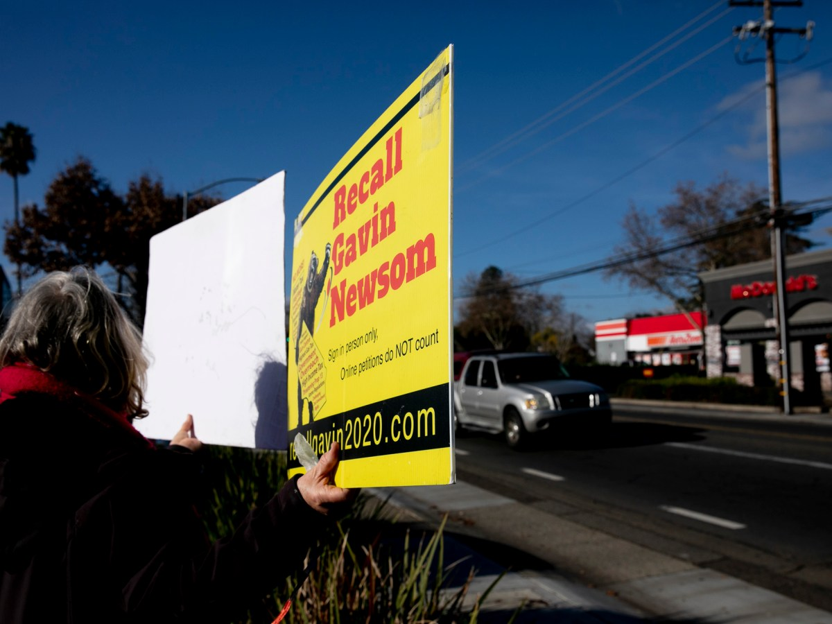 A recall Newsom volunteer carries a sign during a petition signing event at SaveMart in Sacramento on Jan. 5, 2021. Photo by Anne Wernikoff, CalMatters