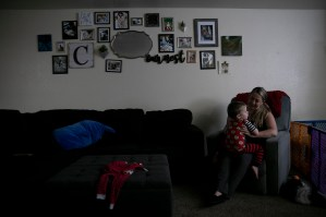 """Miranda Griswold cuddles her three-year-old, Rhys, before bedtime at their Merced home on July 8, 2021. """"Six weeks is nothing,"""" Griswold said of the current family leave allotment. """"It's barely time to recover [from C-section] and on top of navigating breast feeding."""" Photo by Anne Wernikoff, CalMatters"""