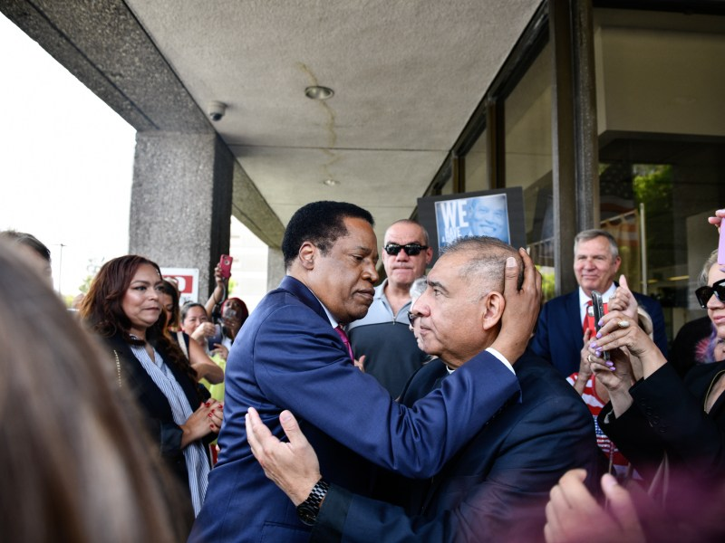 Conservative radio talk show host Larry Elder, embraces Bishop Juan Mendez from Churches In Action during a rally in Norwalk, on July 13, 2021. Elder announced his bid as a recall candidate for governor of California. Pablo Unzueta for CalMatters