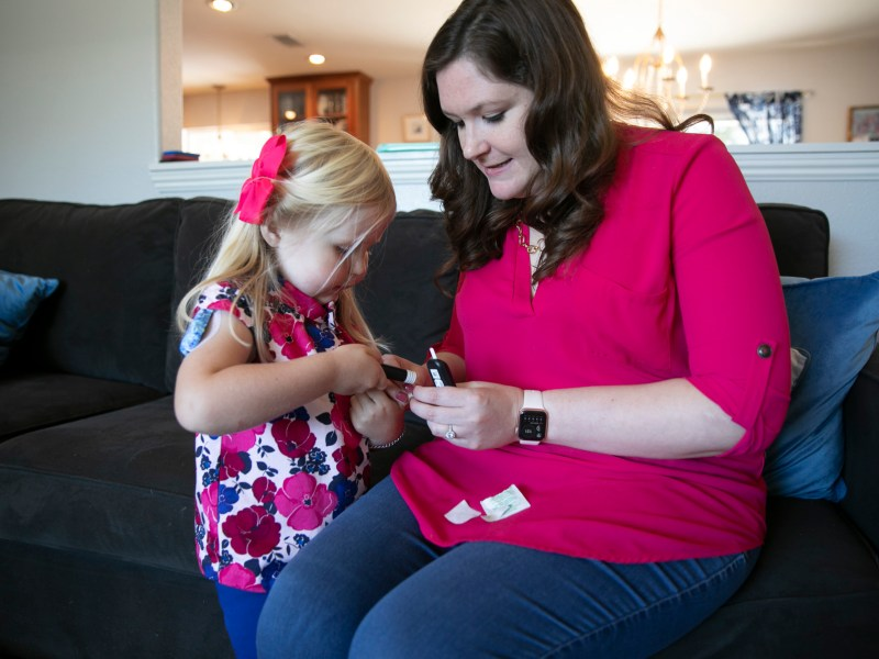 Noelle Tuominen helps Eleanor, 4, test her blood glucose levels at their Livermore home. Eleanor, who was diagnosed with type 1 diabetes at one year old has been doing her own finger pricks since the age of two. Photo by Anne Wernikoff, CalMatters