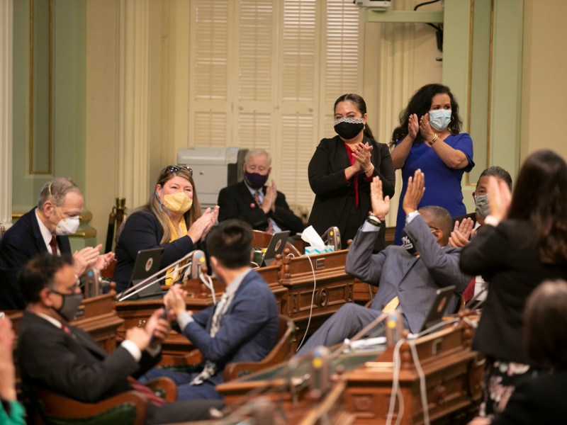 """Assemblymembers applaud after passing a raft of budget """"trailer bills"""" on the final day before summer break on July 15, 2021. Photo by Anne Wernikoff, CalMatters"""