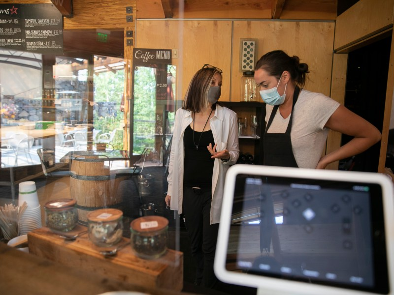 """Hotel owner Patty Baird, left, speaks with server Krisann Smith while checking the kitchen at Cedar House Sport Hotel in Truckee on July 23, 2021. Baird works long days, frequently including double shifts, in order to prevent burnout among her employees who she describes as """"family."""" Photo by Anne Wernikoff, CalMatters"""