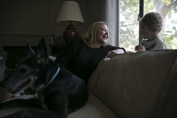 Elizabeth Olson and her son Lucas, 2, sit in the living room of their newly-purchased home in the Land Park neighborhood of Sacramento on Aug. 4. 2021. Olson hopes to renovate the house into a duplex so to make room for her aunt and her partner, who currently live in the home. Photo by Anne Wernikoff, CalMatters