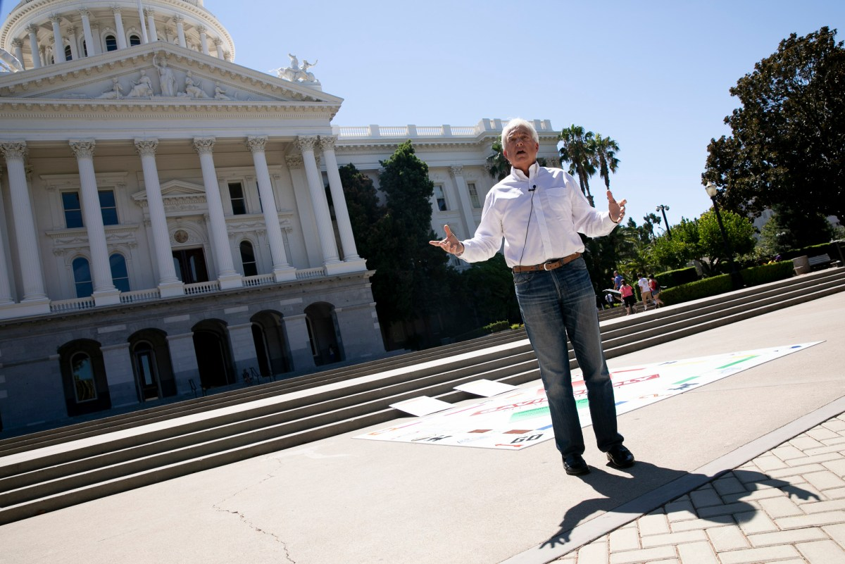 """Republican recall candidate John Cox holds a press conference at the state capitol on Aug. 5, 2021. Cox brought a giant Monopoly board dubbed """"Gavinopoly"""" to outline points in his proposed budget. Photo by Anne Wernikoff, CalMatters"""