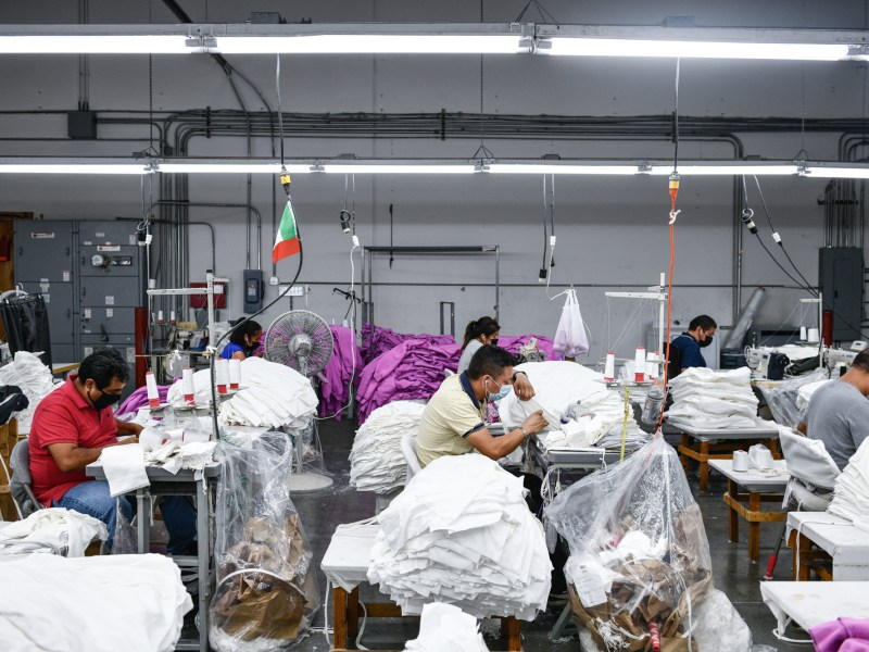 Rows of sewing machines are lined up in seperate stations inside an apparel factory, Ustrive Manufacturing, in Los Angeles on August 18, 2021. Photo by Pablo Unzueta for CalMatters
