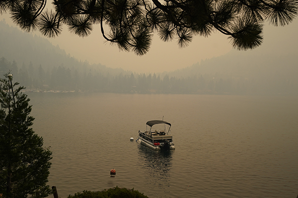 Smoke from the Caldor Fire, shrouds Fallen Leaf Lake near South Lake Tahoe on Aug. 24, 2021. The massive wildfire, that is over a week old, has scorched more than 190 square miles, and destroyed hundreds of homes since Aug. 14. It is now less than 20 miles from Lake Tahoe. Photo by Rich Pedroncelli, AP Photo