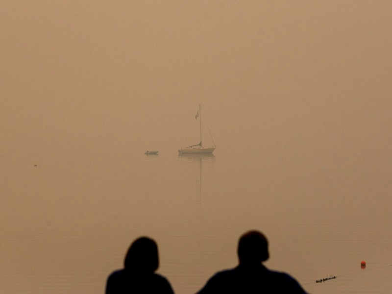 A couple looks out on Lake Tahoe, which is blanketed by smoke from the Caldor Fire, in South Lake Tahoe on Aug. 27, 2021. Photo by Noah Berger, AP Photo