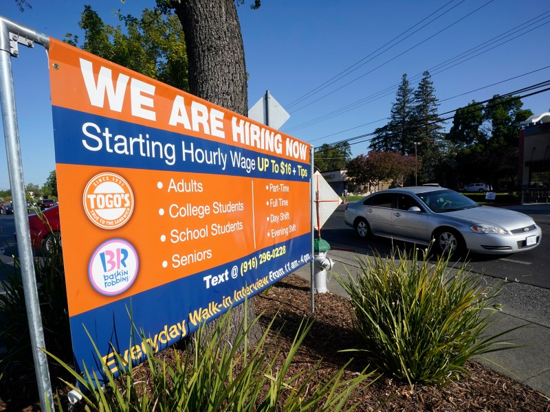 A car passes a hiring banner in Sacramento, July 16, 2021. Hiring in California slowed down in June 2021 as employers in the nation's most populous state tried to coax reluctant workers back into their pre pandemic jobs before the nation's expanded unemployment benefits expire in September. Photo by Rich Pedroncelli, AP Photo