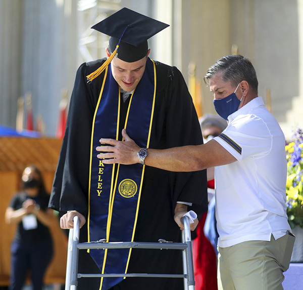 Robert Paylor, left, is assisted by Tom Billups, right, as he walks across the stage of the Greek Theater after receiving his diploma during a commencement ceremony for business students at U.C. Berkeley on Aug. 29, 2021. Paylor, a Cal rugby player was injured in a 2017 game that left him paralyzed from the neck down. Photo by Aric Crabb, Bay Area News Group