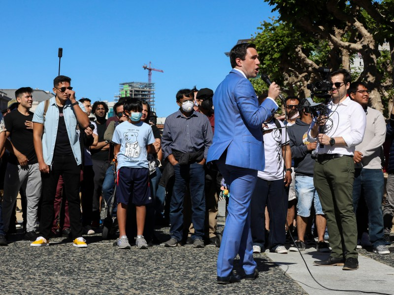 """Newsom recall candidate Kevin Paffrath reads his statement from an iPad as he addresses a crowd at a """"Meet Kevin for Governor Campaign Rally"""" at San Francisco Civic Center Plaza on .June 12, 2021. Photo by Yalonda M. James, San Francisco Chronicle, Polaris"""