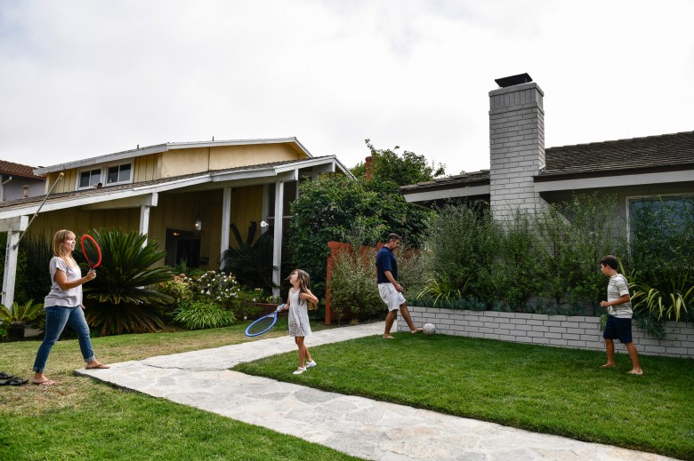 Cynthia Rojas and Kevin Jardim play with their kids in the front yard of their Culver City home. According to the couple, if the Newsom recall doesn't succeed, they may move to another state.