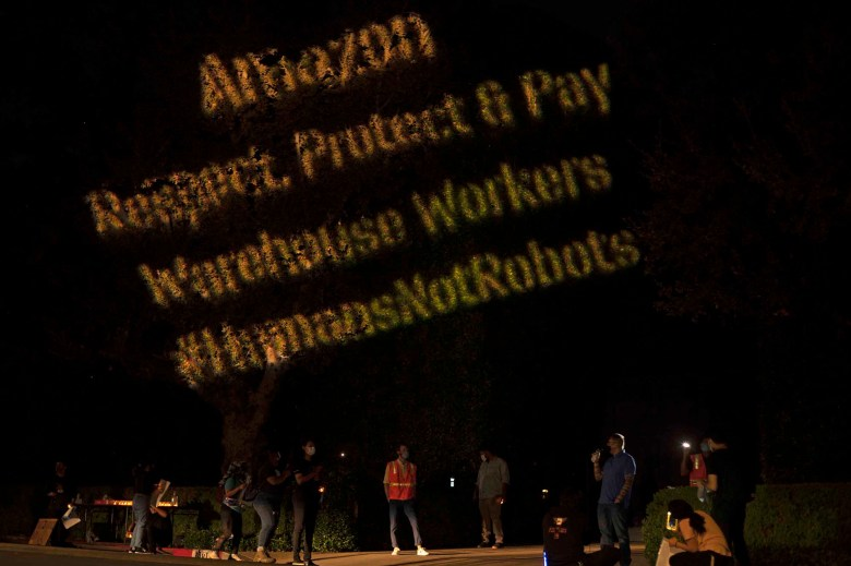 """Protestors project the words """"Amazon respect, protect and pay warehouse workers #humansnotrobots"""" onto the shrubs outside Amazon CEO Jeff Bezos' house during a Prime Day protest on Oct. 13, 2020. Photo by Tash Kimmell for CalMatters"""