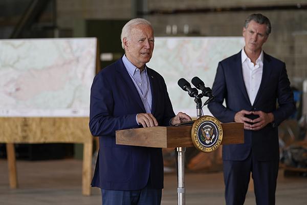 Gov. Gavin Newsom listens as President Joe Biden speaks about recent wildfires, at Sacramento Mather Airport, Sept. 13, 2021, near Sacramento. Photo by Evan Vucci, AP Photo