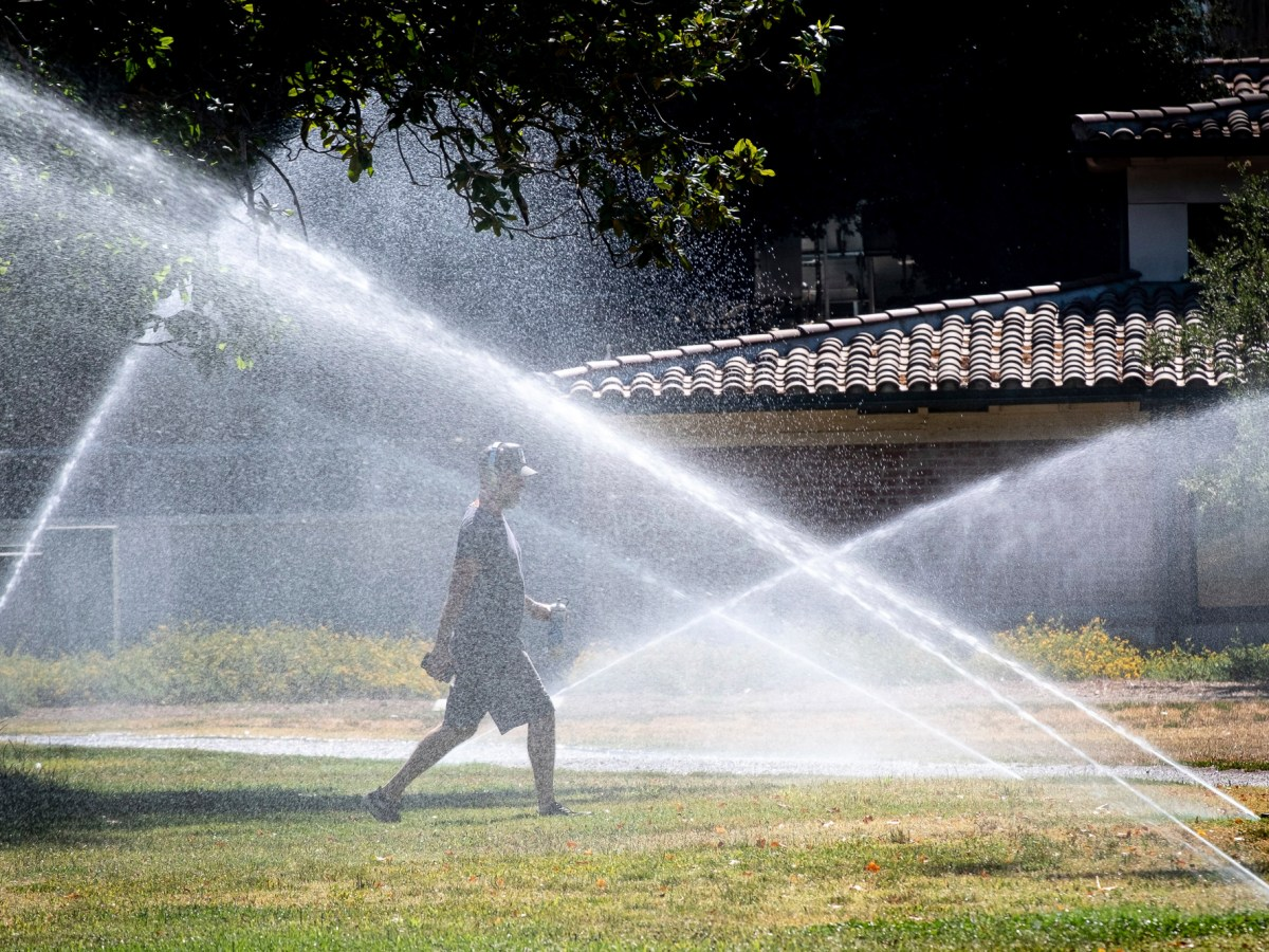 A walker at North Hollywood park gets refreshed along the walking path from the park sprinklers Monday, June 28, 2021. Photo by David Crane, The Orange County Register via AP