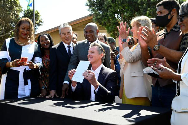 Gov. Gavin Newsom signs SB 796, a bill to return Manhattan Beach land to descendants of its original Black owners, the Bruce family, in Manhattan Beach on Sept. 30, 2021. Photo by Brittany Murray, Pres-Telegram/SCNG