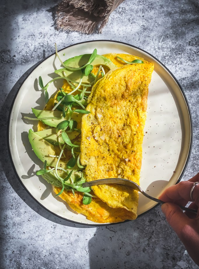 avocado and egg omelette on plate with fork