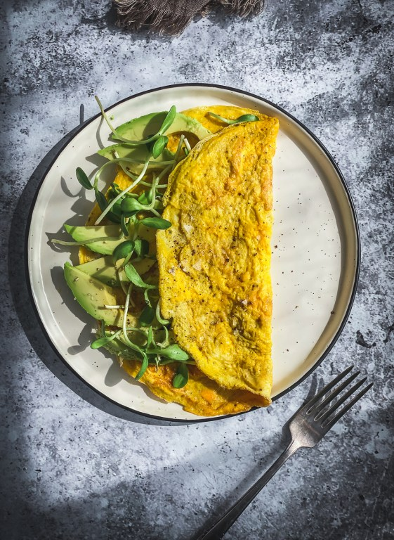 avocado and greens omelette on table with fork