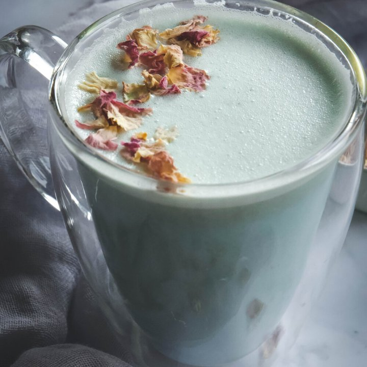 Cardamom Moon Milk in clear mug topped with rose petals
