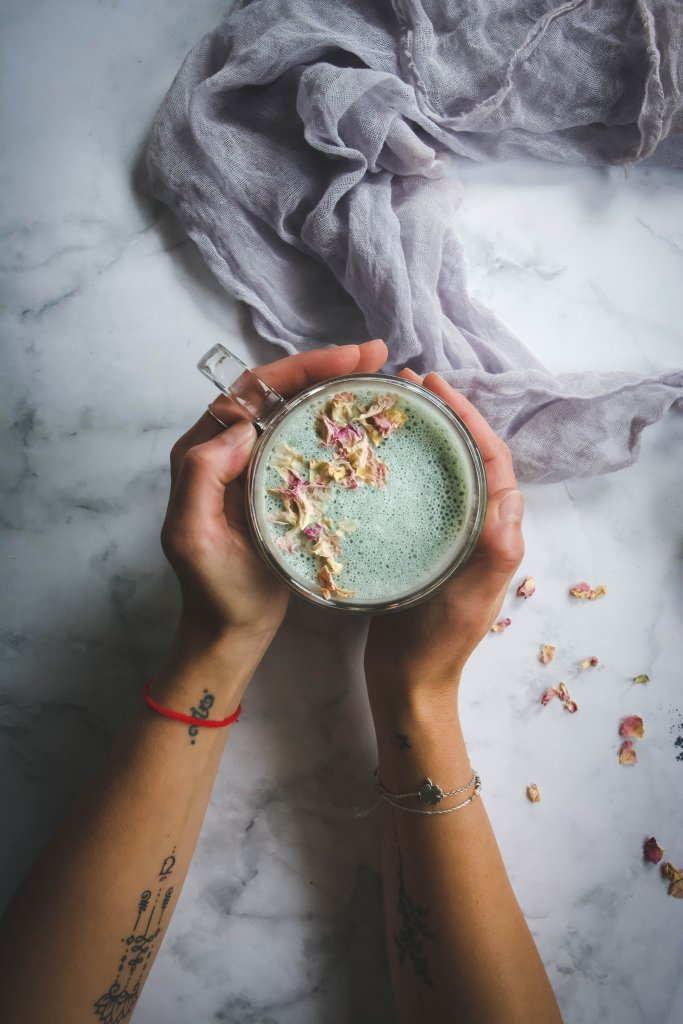 Cardamom Moon Milk in clear mug held in hands with light purple napkin on marble table