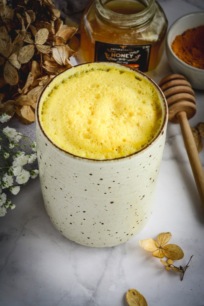 turmeric milk in mug, honey, dry flower