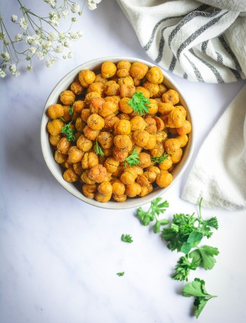 Crispy chickpeas in bowl topped with parsley with baby's breath and napkin