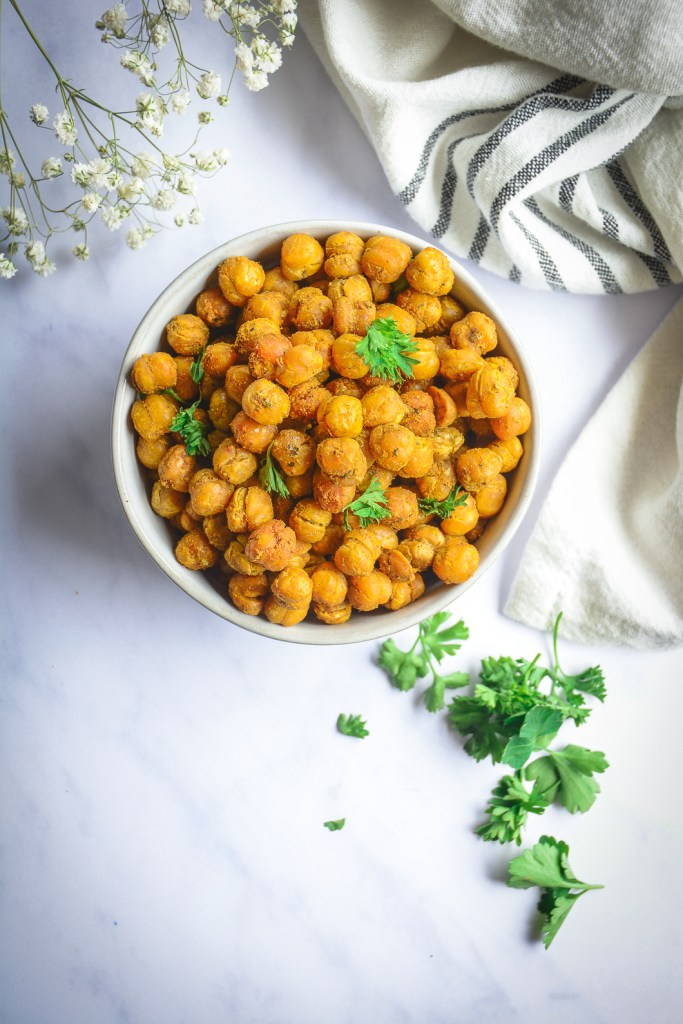 Crispy roasted chickpeas in bowl with parsley and black and white napkin