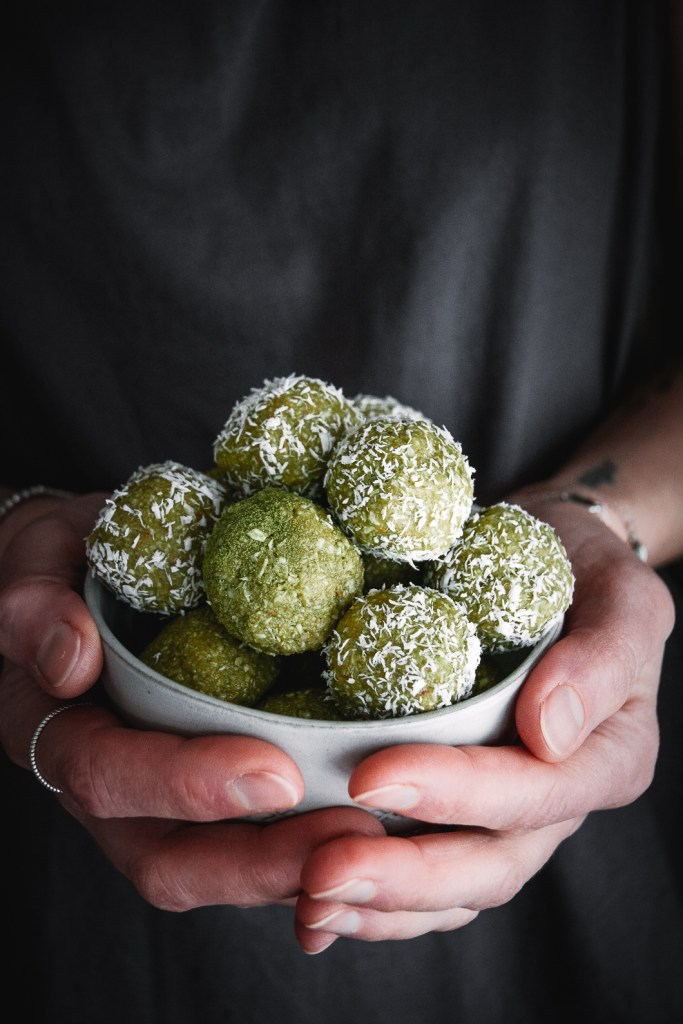 matcha balls covered with shredded coconut in bowl, held in hands