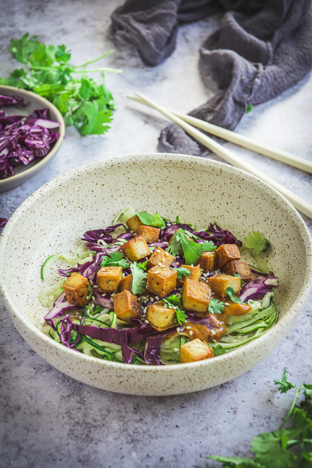 Zoodles with Thai Peanut Sauce and Tofu on table with cilantro and chopsticks, red cabbage and napkin